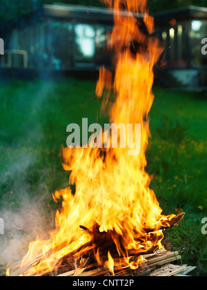 Bonfire burning in backyard - Stock Photo