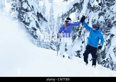 Skiers high-fiving on snowy mountain - Stock Photo