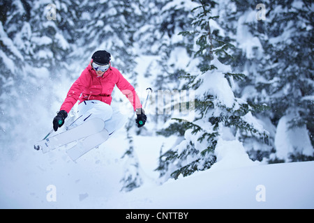 Skier jumping on snowy slope - Stock Photo
