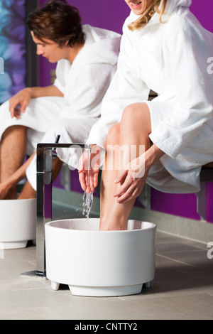 Couple - man and woman - having hydrotherapy water footbath in spa setting - Stock Photo