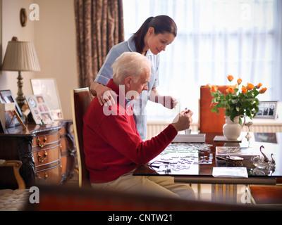 Nurse and older man doing jigsaw puzzle - Stock Photo