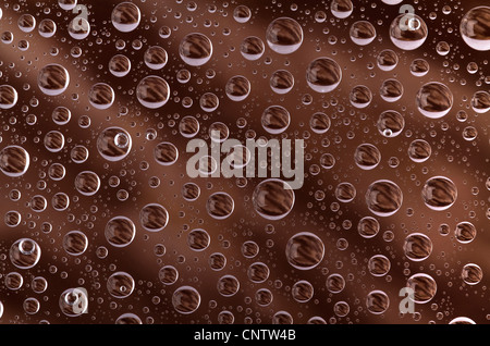 water drops over brown background, on the glass surface - Stock Photo