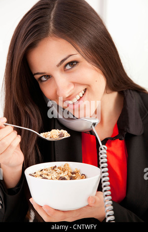 Businesswoman eating on telephone - Stock Photo