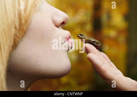 Girl kissing tiny frog in forest - Stock Photo