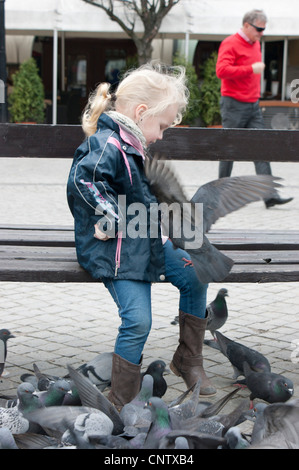 Small girl feed many pigeons on central square - Stock Photo