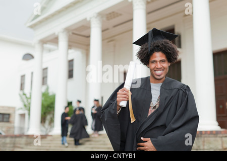 Graduate holding his degree on campus - Stock Photo