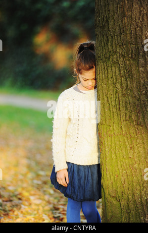 Girl leaning on tree in park - Stock Photo