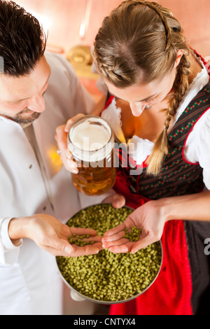 Woman in Tracht and brewer with beer stein and hops in her brewery - Stock Photo