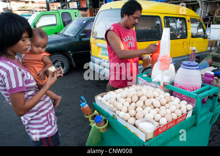 Woman with her baby, she is buying Balut, a fertilized duck embryo from a roadside vendor. Carbon Market, Cebu City, - Stock Photo