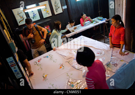Horizontal interior aerial view of ladies selling their embroidered table linen to a group of Western tourists, - Stock Photo