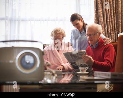 Nurse reading with older couple - Stock Photo
