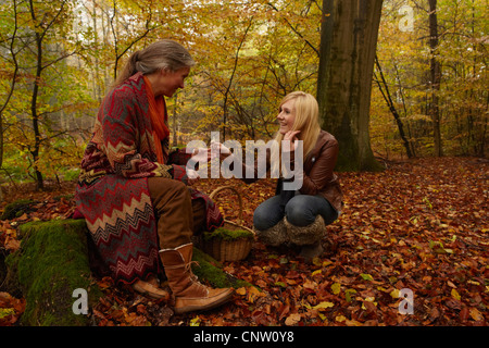 Mother and daughter talking in forest - Stock Photo