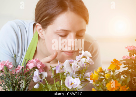 Woman smelling flowers plants indoors - Stock Photo
