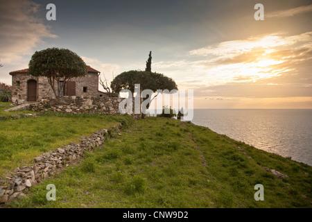Stone house overlooking coastline - Stock Photo