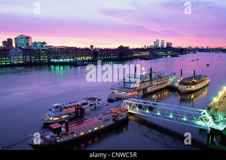 England, London, Night View of Boats on the Thames River with Docklands and Canary Wharf Skyline in Background - Stock Photo
