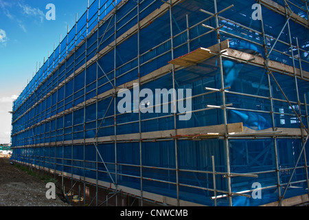 Building site scene with scaffolding and safety netting. - Stock Photo
