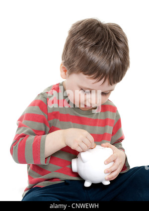 Boy putting money in piggy bank - Stock Photo