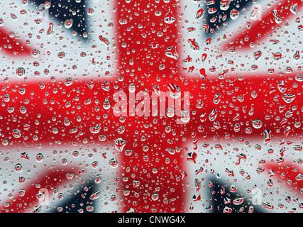 Raindrops on glass in front of a Union jack flag - Stock Photo