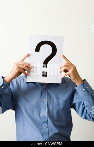 Man with question mark covering face. - Stock Photo