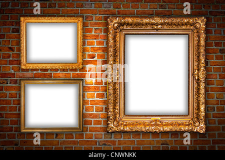 Old ornate golden frames hanging on a brick wall. - Stock Photo