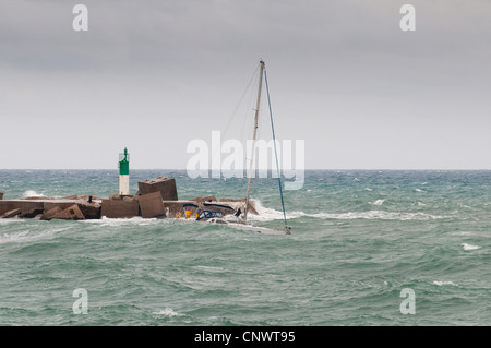 sailboat at stormy surge, in front of breakwaters with beacon, France, Languedoc-Roussillon, S�te - Stock Photo