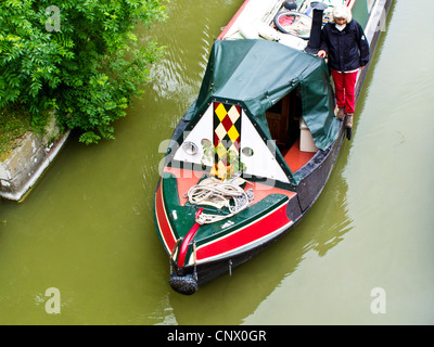 Narrowboat passing under a bridge near Pewsey Wharf on the Kennet and Avon Canal in Wiltshire, England, UK - Stock Photo