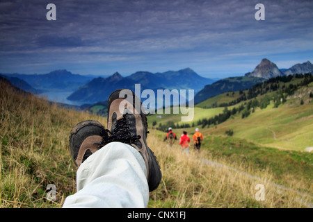 feet with hiking shoes in front of the mountain panorama, Switzerland, Berner Alpen, Alps - Stock Photo