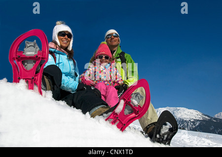 family of three sitting in the snow at a slope during snowshoeing on holidays in the mountains, France - Stock Photo