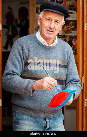 Elderly man panting a wooden model ship, Monopoli, Italy - Stock Photo