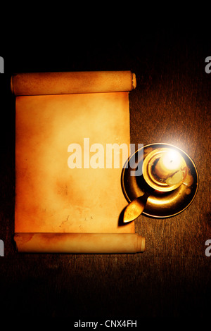 Old scroll and candle on wooden table - Stock Photo