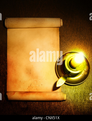 Ancient scroll and candle on wooden table - Stock Photo