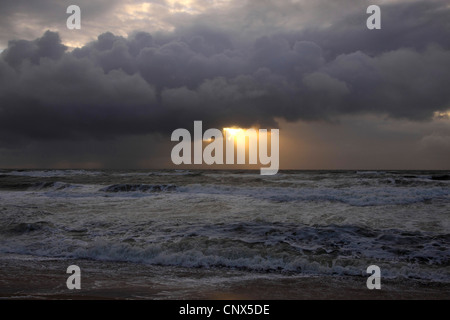 sun beam breaking through rain clouds over the North Sea, Germany, Sylt, Rantum - Stock Photo