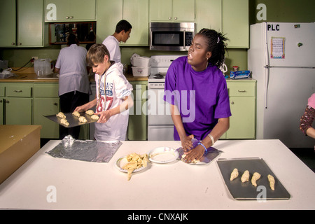 Blind African-American preteen girl makes rolls by touch  in a cooking class at the Blind Children's Learning Center, - Stock Photo