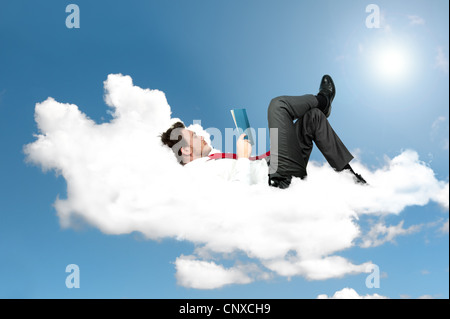 Businessman that read a book on a cloud - Stock Photo