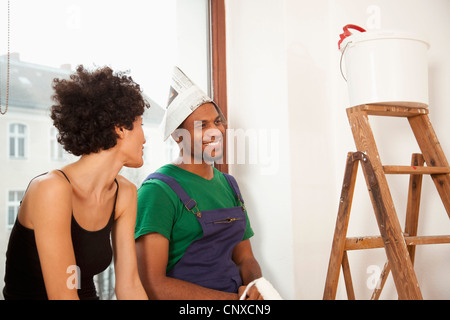 A couple taking a break from painting their apartment - Stock Photo