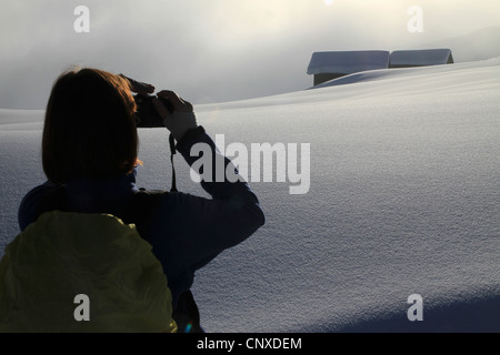 Hiker takes photograph of snowy log cabins in the distance - Stock Photo