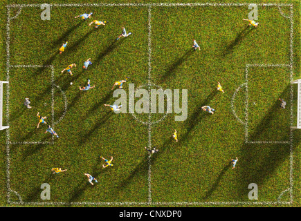 Miniature figurines of two soccer teams playing a soccer match, directly above - Stock Photo