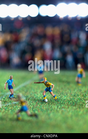 Miniature figurines of two soccer teams playing a soccer match - Stock Photo