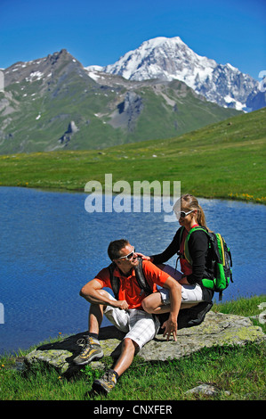 two wanderer sitting at a mountain lake, Mont Blanc in background, France, Savoie, Val d'Aosta - Stock Photo