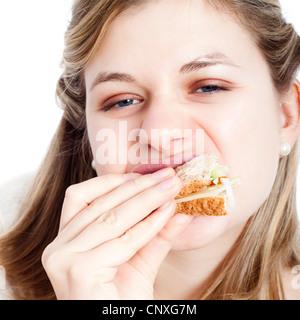 Close up of young woman enjoying eating sandwich. - Stock Photo