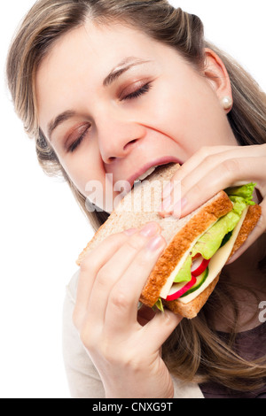 Beautiful young happy woman eating sandwich, isolated on white background. - Stock Photo