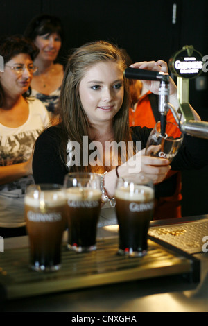 Visitor learning how to pour the 'Perfect Pint', Guinness Storehouse, Dublin, Ireland - Stock Photo