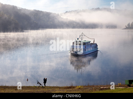 excursion boat on Henne storage lake in morning mist, Germany, North Rhine-Westphalia, Sauerland, Meschede - Stock Photo