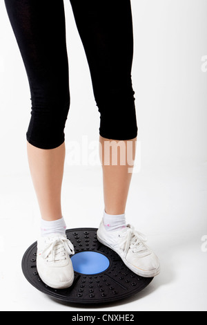 Girl on wobble board - Stock Photo