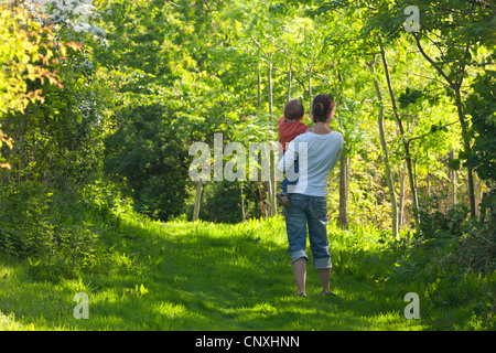 Mother and one year old son standing in a deciduous woodland, Cutteridge Wood, Devon, England. Spring (April) 2011. - Stock Photo