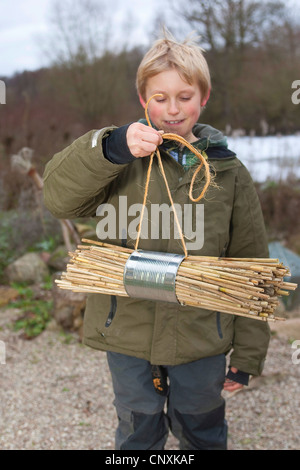 boy collecting material for building a insect hotel, Germany - Stock Photo