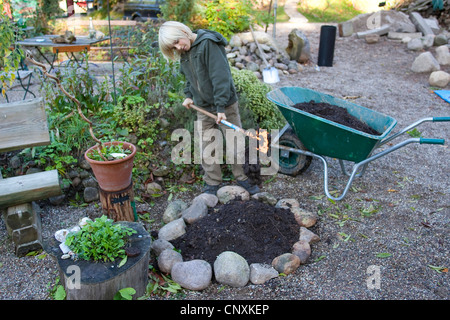 boy building a herb spiral in a garden, Germany - Stock Photo
