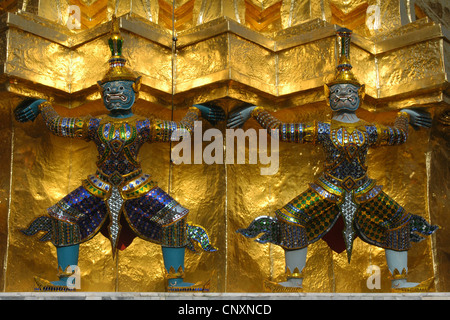 Yaksha Demon statues guard the golden chedi in Wat Phra Kaew in Bangkok, Thailand. - Stock Photo