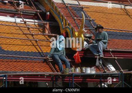 Workers repair roof of one of the temple in Wat Phra Kaew in Bangkok, Thailand. - Stock Photo