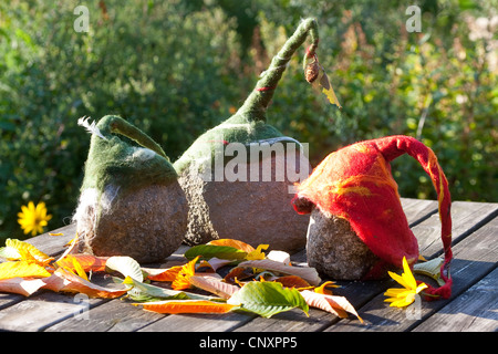 'felt stone trolls' serving as garden decoration: three natural stones equipped with caps of felted wool standing - Stock Photo